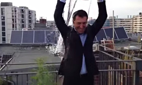 Cem Özdemir pours a bucket of water on his head, dousing a cannabis plant beside him.