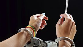 Enslaved by drugs Handcuffed female hands holding marijuana cigarette